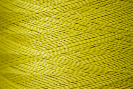 close up: Close up of a spool of synthetic green thread