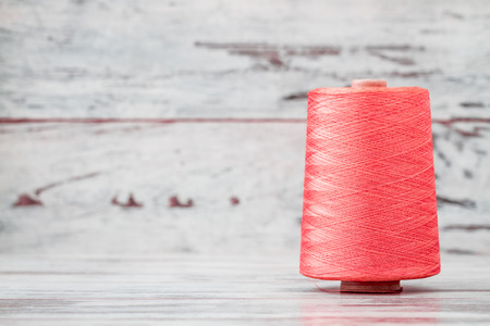 nylon string: Spool of synthetic pink thread on white wooden background Stock Photo