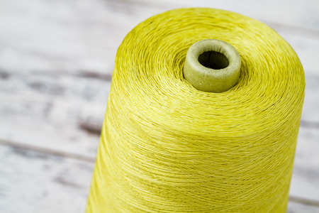 synthetic fiber: Spool of synthetic green thread on white wooden background Stock Photo