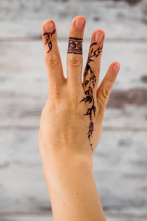 asian wedding: Woman hand without nail polish painted with floral figures using black henna Stock Photo