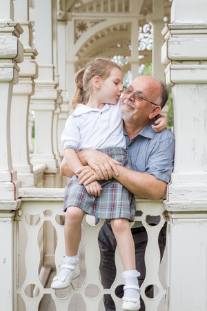 Little girl with school uniform and her grandfather in green park photo