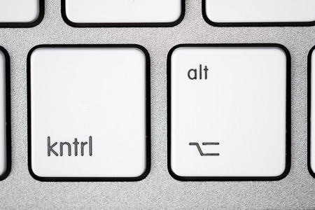 alt: Close up of a white, gray computer keyboard. Focus on kntrl and alt.