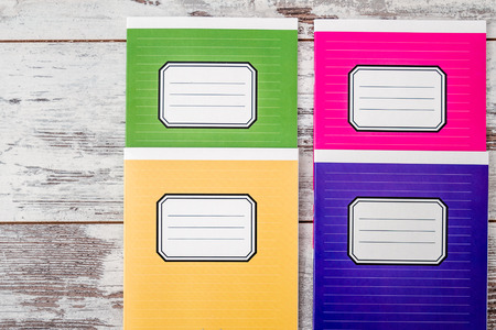 Colorful notebooks with name label on cover on white wooden background