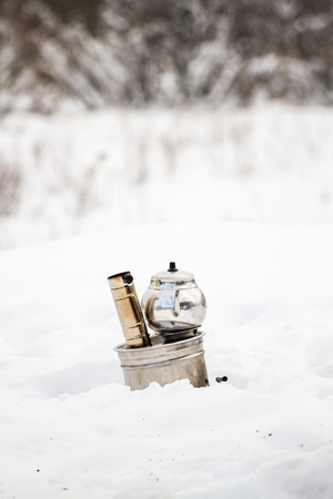 covered in snow: Daytime view of a portable stove in a picnic field covered with snow Stock Photo