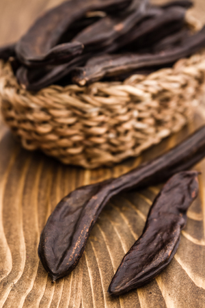 carob: Group of dried carob pods, Ceratonia Siliqua, on wooden background