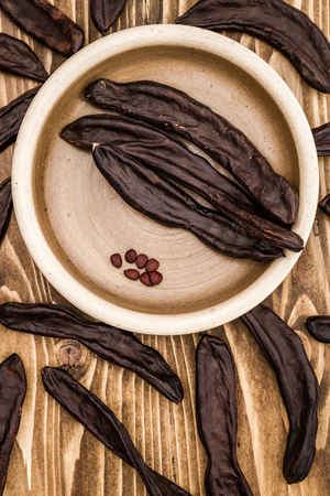 Group of dried carob pods, Ceratonia Siliqua, on wooden background