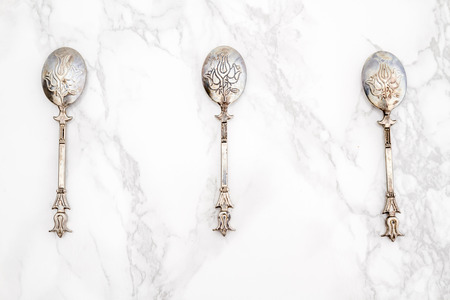 grunge silverware: Old vintage dessert spoons with ornament on white marble