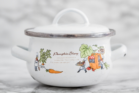 antique dishes: Empty small white vintage enamel saucepan with pumpkin design on white marble background Stock Photo