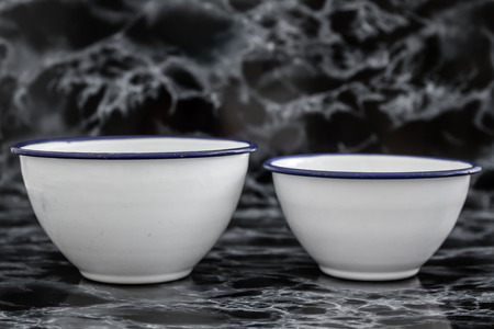 antique dishes: Big white vintage enamel bowls on black marble background Stock Photo
