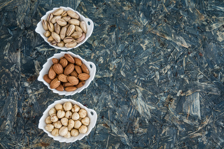salted: Pistachios, almonds and hazelnuts in white bowls on blue background