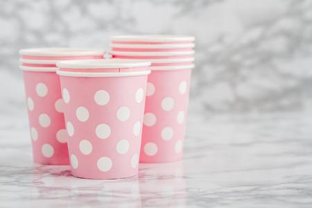 Gruppo di bicchieri di carta usa e getta rosa su sfondo di marmo bianco