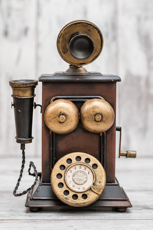 corded: Retro phone as home decoration on white wooden background