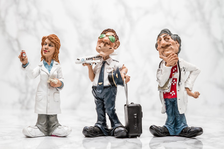 statuettes: Collection of statuettes of different profesions on white marble background