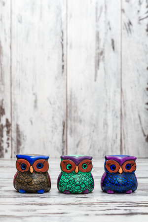 statuettes: Collection of statuettes of colorful owls  on white wooden background