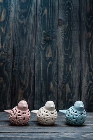 statuettes: Statuettes of white, blue and pink birds on blue wooden background