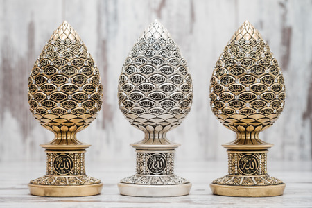 coran: Silver and Golden Religious statuettes with the names of Allah, the God written on them Stock Photo