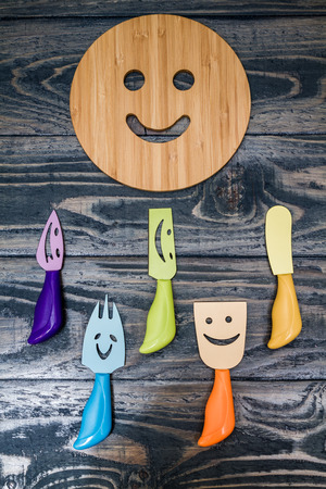 trivet: Round wooden trivet with smiley face on blue wooden background Stock Photo