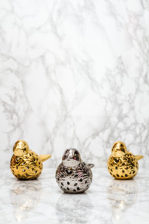 statuettes: Statuettes of silver and golden birds on white marble background