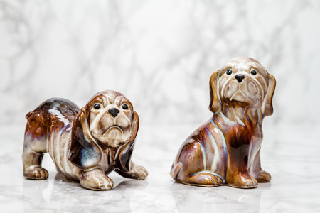statuettes: Statuettes of cute dogs  on white marble background Stock Photo