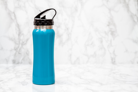 thermos: Blue steel thermos on white marble background