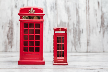 phonebooth: Decorative money box as classic British red phone booth on white wooden background
