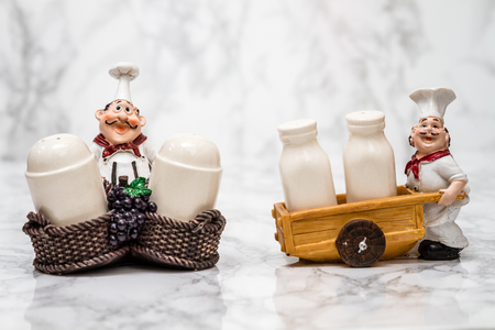 statuettes: Collection of statuettes of cooks with shakers on white marble background