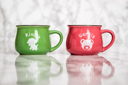 enamel: Colorful ceramic mugs with enamel look on white marble background