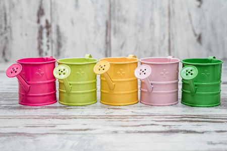 wateringcan: Simple colorful metallic watering cans on white wooden background