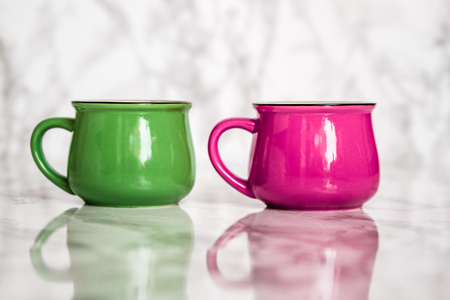 Colorful ceramic mugs with enamel look on white marble background