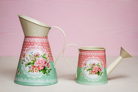 wateringcan: Simple colorful metallic watering cans on pink background Stock Photo