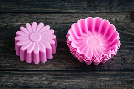 decoracion de pasteles: Pila de coloridos moldes para pasteles de silicio en el fondo de madera azul