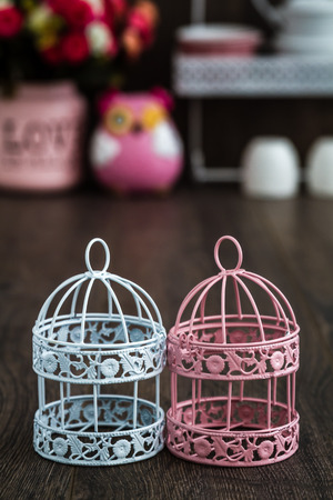 candleholder: Pink and blue wrought iron candle holders on wooden background