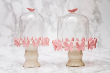 a jar stand: Empty bell jars with pink butterfly design on white marble Stock Photo