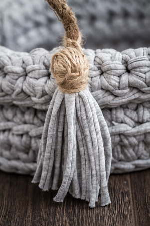 oft: Gray decorative knitted basket on wooden background