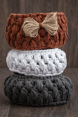 oft: Decorative knitted baskets with ribbons on wooden background