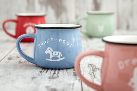enamel: Colorful ceramic mugs with enamel look on white wooden background