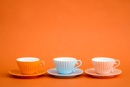 Cute colorful coffee cups on orange background with copy space Stock Photo
