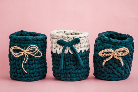 Decorative knitted green baskets with ribbons on pink wooden background