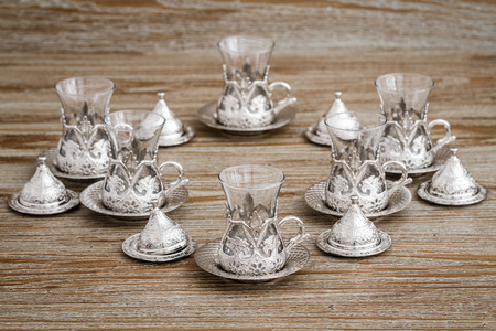 Traditional silver coffee cup set in a tray on brown wooden background