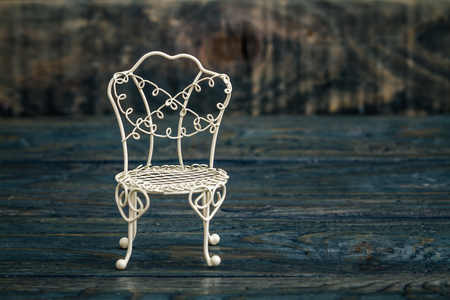 brightness: Decorative mini wrought iron chair on blue wooden background