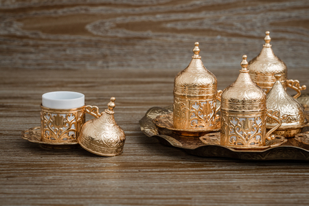Traditional golden coffee cup set in a tray on brown wooden background