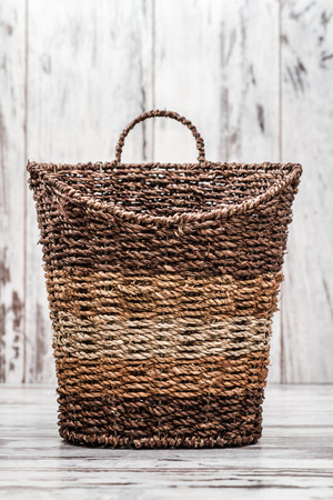 basketry: Brown knitted basket on white wooden background