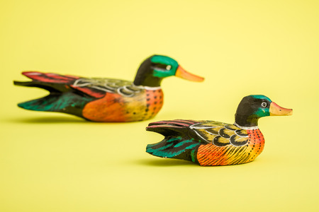 decoy: Hand made wooden ducks for home decoration on yellow background Stock Photo