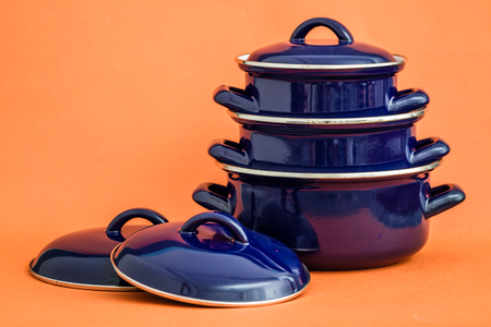 New and clean covered dark blue saucepans on orange background Reklamní fotografie - 76341053