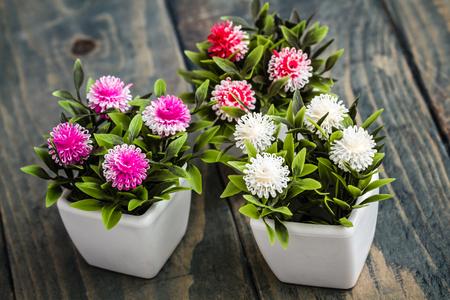 Artificial flowers in white flowerpots on blue wooden background