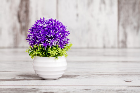 Artificial purple plant with copy space on white wooden background Stock Photo