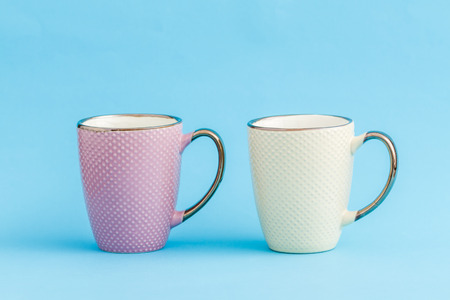 Colorful coffee mugs on blue background
