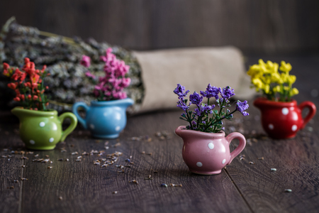 Artificial little yellow, purple and red flowers in little flowerpots on  wooden background