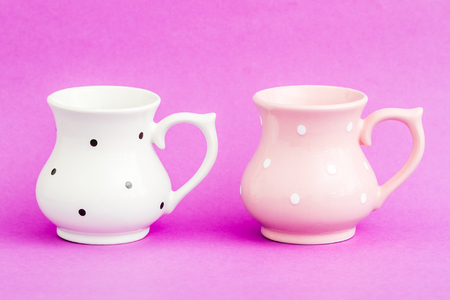 White and pink  vintage buttermilk cups with black dot pattern on purple background