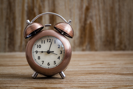 Old fashioned copper alarm clock on brown wooden background Stock Photo